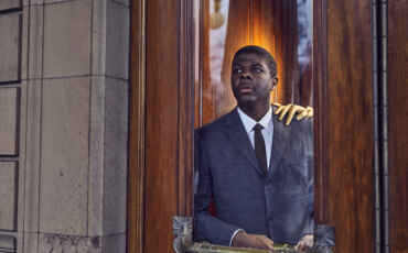 Black man with gold hand resting on shoulder